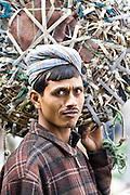 INDIA, NEW DELHI:  Young Indian man working as a day laborer carries a basket through the vegetable market in New Delhi.