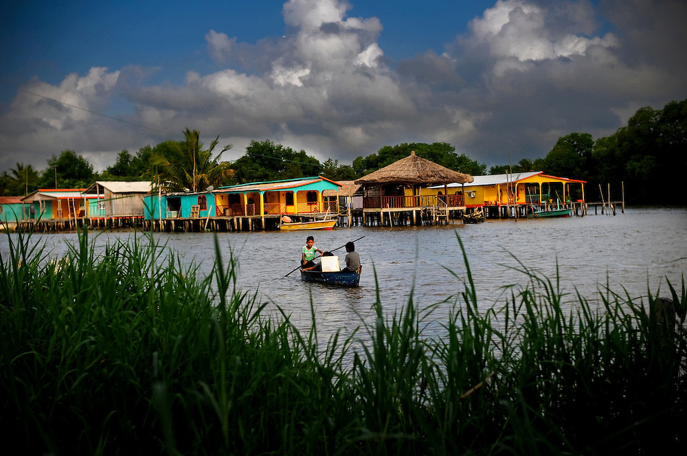 """Sinamaica Lagoon, situated along a notorious Venezuela/Colombia waterway used by narco-traffickers, is one of the last remaining ´floating villages´on earth, where habitants including indigenous """"Añú"""" indians live in houses above water; and travel to work, school, etc. via wooden canoes or small motor boats. Life in the lagoon is currently threatened by social issues such as severe poverty, water contamination and global warming."""