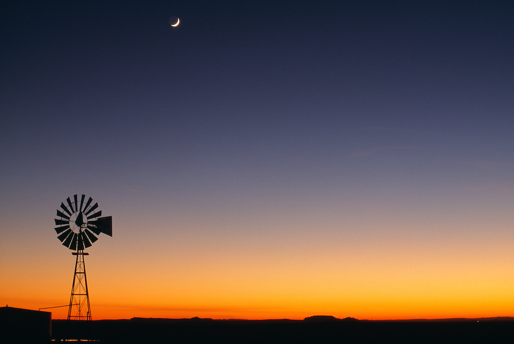 Silhouette of wind turbine at night