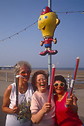 Three laughing ladies hold up their sticks of rock beneath a seaside character on the seafront at Blackpool, on 18th July 1993, Blackpool, Lancashire, England. In 1887, sugar-boiling factory owner Ben Bullock bought some plain stick candy band had the idea of putting 'Blackpool Rock' through the centre of the rock. Now a major industry in the holiday season in Britain and many seaside towns have their versions with their own names running through the rock. Modern seaside rock is thicker, about 1 inch, and more solid than the original form. Its sugar content is nowadays a reason not to buy as much, the adverse effects on teeth from sugar and colouring by the confectionary industry being a main reason for its decline.