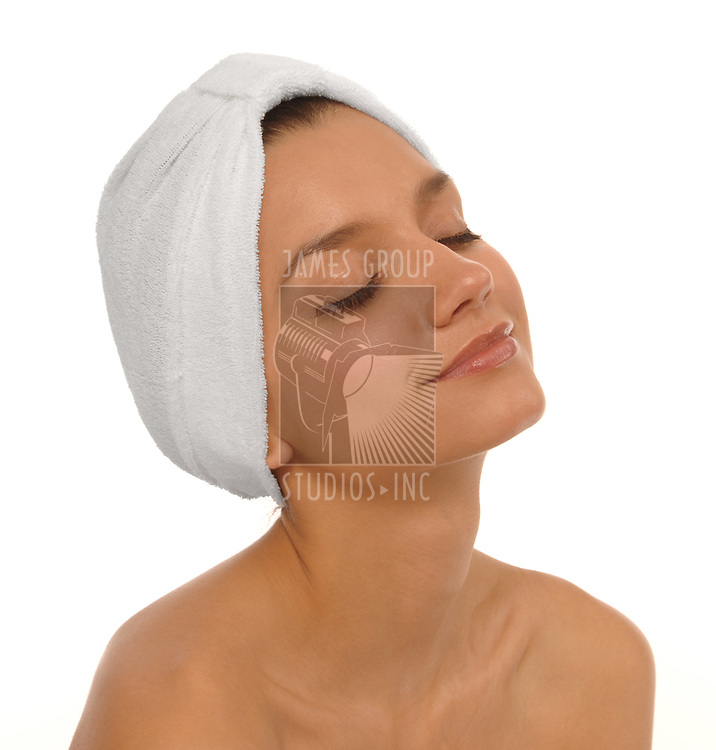 Beautiful young woman looking relaxed with her eyes closed wearing a white spa turban over a white background