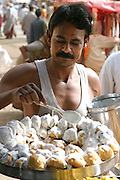 A baker in Ujjain, India, drips milky sweet topping onto sweet fried dough to sell to passersby. He and other vendors reaps the benefits of the arrival of millions of pilgrims for the once-every-12-year occurrence of Kumbh Mela festival in Ujjain for observant Hindus.(Supporting image from the project Hungry Planet: What the World Eats)