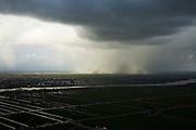 Nederland, Zuid-Holland, Alblasserwaard, 04-03-2008; de Lek gezien vanuit de Alblasserwaard, Polder Streefkerk in de voorgrond; slecht weer aan de andere kant van de rivier boven Polder Bergambacht; veenweide landschap, stroken, verkaveling, kavel, dreigende wolken, regenwolken, dreigen, dreigend, sluier, regensluier, wolken, noodweer. .luchtfoto (toeslag); aerial photo (additional fee required); .foto Siebe Swart / photo Siebe Swart
