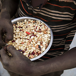 A refugee child shows kernels of maize and beans he collected from the ground at a food distribution center in the Bidi Bidi refugee center in Uganda. <br />
