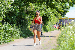© Licensed to London News Pictures. 20/05/2020. London, UK. A woman walking in Markfield Park, Tottenham, north London on a warm and sunny day in London. The government has relaxed the rules on the COVID-19 lockdown, allowing people to spend more time outdoors whilst following social distancing guidelines. According to the Met Office, 27 degrees celsius is forecast for today.  Photo credit: Dinendra Haria/LNP
