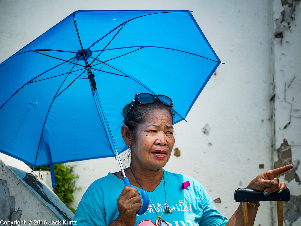 29 SEPTEMBER 2016 - BANGKOK, THAILAND: A resident of Pom Mahakan community walks down the street in front of the fort during a rally Thursday. Forty-four families still live in the Pom Mahakan Fort community. The status of the remaining families is not clear. Bangkok officials are still trying to move them out of the fort and community leaders are barricading themselves in the fort. The residents of the historic fort are joined almost every day by community activists from around Bangkok who support their efforts to stay.     PHOTO BY JACK KURTZ