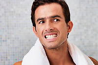 Portrait of handsome man looking on the mirror while checking on his teeth