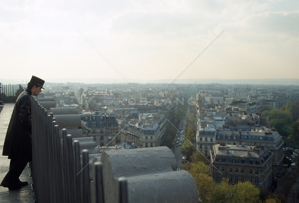 French policeman looking at Paris from a building rooftop