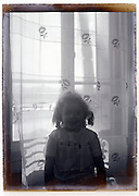 glass plate image of young girl in front of window 1930s