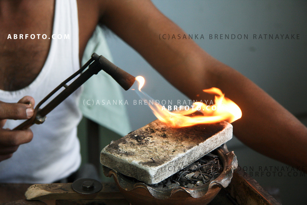 A jeweler uses a small blow torch to melt metal to surround a gem