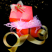 A partially opened boxed and wrapped present with an ornate bow to symbolize a gift. The box is lit from the inside to symbolize mystery and anticipation. Stars and dust are flowing out of the box.