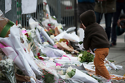 © London News Pictures. 14/11/2015. A young boy laying flowers near Bataclan theatre  the day after multiple terror attacks on the French capital. Photo credit: Guilhem Baker/LNP