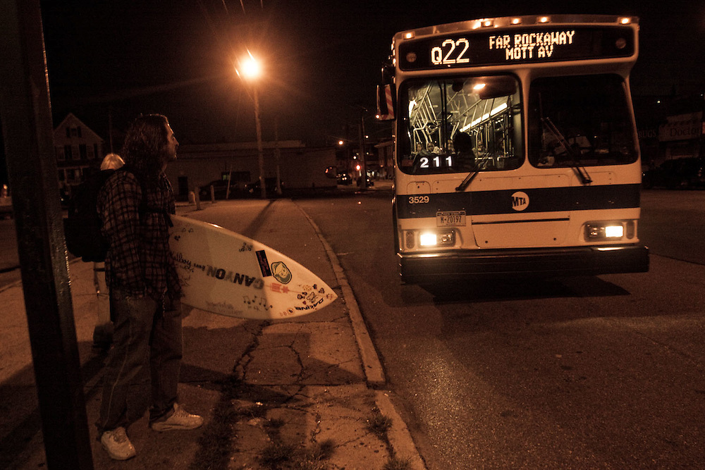 A surfer awaits the Q22 bus to take him back to Manhattan, Rockaway Beach, Queens, NY.