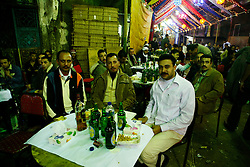 """In the Moqattam area of greater Cairo, Egyptians hold an engagement party for someone from the community. This particular community are referred to as the """"Zabaleen,"""" or trash collectors. Mostly Coptic Christians, the Zabaleen are responsible for collecting and recycling most of Cairo's waste. Weddings, engagement parties, and other events are celebrated in the neighborhood streets. Food, alcohol and hashish were served to people who came to celebrate the occasion while music played and three belly dancers performed for the all-male crowd.///Men celebrating the engagement sit, eat, drink and smoke while listening to music and watching the belly dancers perform on stage."""