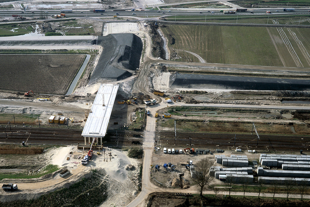 Nederland, Oude Moerdijkpolder, Bredase Dijk, 08-03-2002; spoor emplacement rond Station Lage Zwaluwe, HSL komt parallel aan (en boven) bestaand spoor; aanleg van viaduct (met landhoofden) waarmee de (nieuwe) sporen overgestoken zullen worden, bestaande overweg komt te vervallen; geheel boven: de A16 / A59, deze wordt in het kader van de HSL aanleg ook gereconstrueerd en krijgt 2 x 3 rijstroken; infrastructuur verkeer en vervoer spoor intercity trein mobiliteit transport rangeerterrein wegenbouw landschap (zie ook andere foto's Bredase Dijk);<br /> luchtfoto (toeslag), aerial photo (additional fee)<br /> foto /photo Siebe Swart