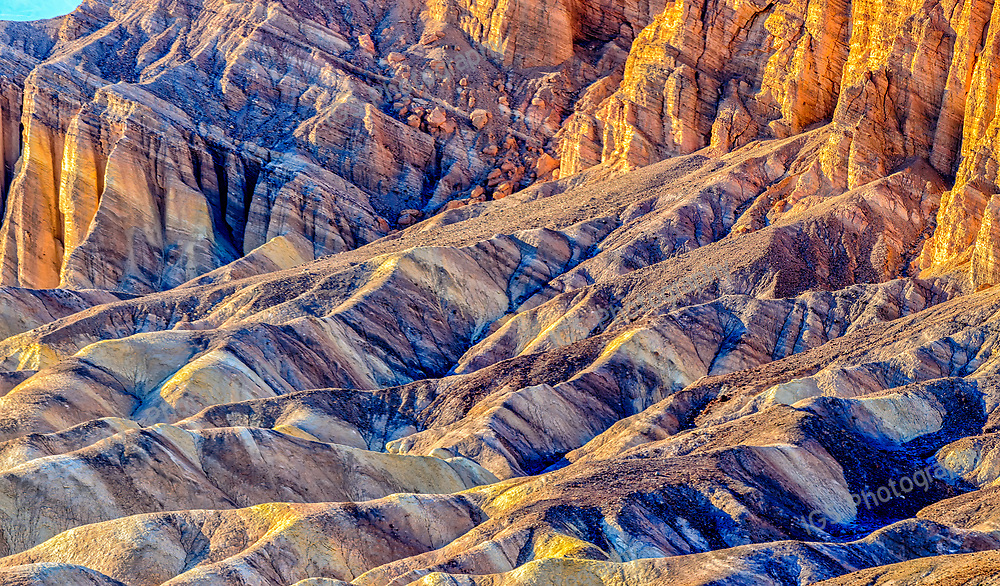Rugged Rock formations during sunset create a colorful landscape at Zabriskie Point