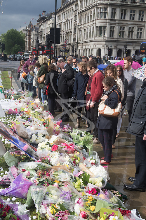 Parliament Square, Westminster, London, June 17th 2016. Following the murder of Jo Cox MP friends and members of the public lay flowers, light candles and leave notes of condolence and love in Parliament Square, opposite the House of Commons. PICTURED: Crowds gather to pay their respects between rain showers.