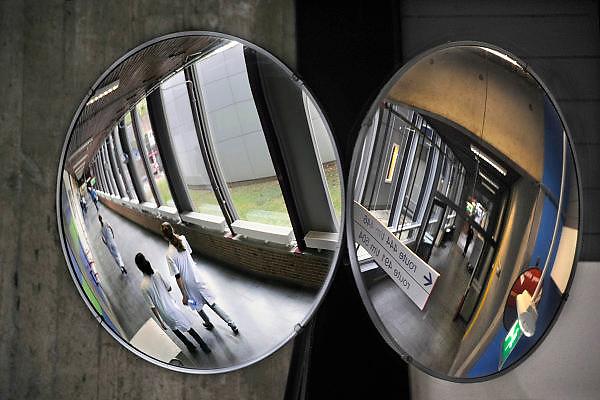 Nederland, Nijmegen, 22-4-2010Ziekenhuismedewerkers, verplaatsen zicht door de gangen, gezien via een spiegel die een kruising zichtbaar maakt. Foto: Flip Franssen