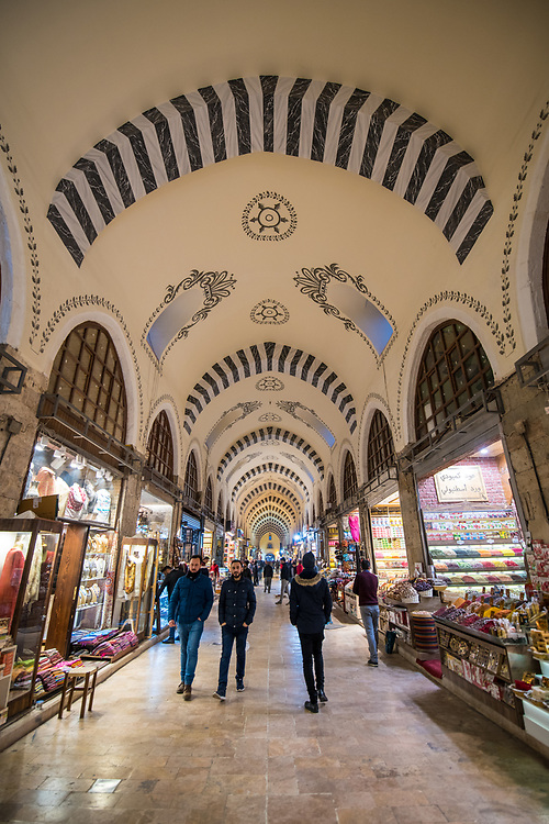 Wide-angle view of the covered arched hallway of the Istanbul Spice bazaar in Turkey with numerous shops lining either side