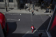 A woman wearing a red suit crosses the road, on 31st July 2017, in Oxford Street, London, England.