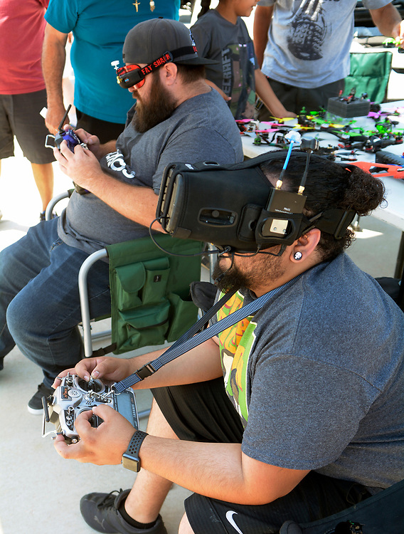 gbs062517e/ASEC - Jules Carter of Albuquerque, left, and Ben Lopez of Albuquerque, members of Southwest Pod Racing wear video goggles as they fly racing drones on a course at the Drone Discovery Day at the Anderson Abruzzo Albuquerque International Balloon Museum on Sunday, June 25, 2017. (Greg Sorber/Albuquerque Journal)