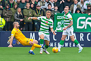Scott Robinson (#17) of Livingston FC tackles Mortiz Bauer (#13) of Celtic FC, as Scott Brown (#8) of Celtic FC watches on during the Ladbrokes Scottish Premiership match between Livingston FC and Celtic FC at The Tony Macaroni Arena, Livingston, Scotland on 6 October 2019.