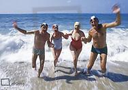 Zwei Seniorenpaare an Strand, laufen aus Wasser, Bewegung (model-released)