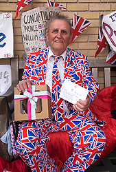 © London News Pictures. 30/04/2015. Royal fan Terry Hutt holding a birthday cake and card sent to him by staff at Kensington Palace on his 80th birthday as he waits outside Lindo Wing of St Mary's hospital in Padding, where The Duchess is due to give birth. **Terry is pictured sitting on the bench he is sleeping on at night outside the Lindo Wing**.  Photo credit: Ben Cawthra/LNP
