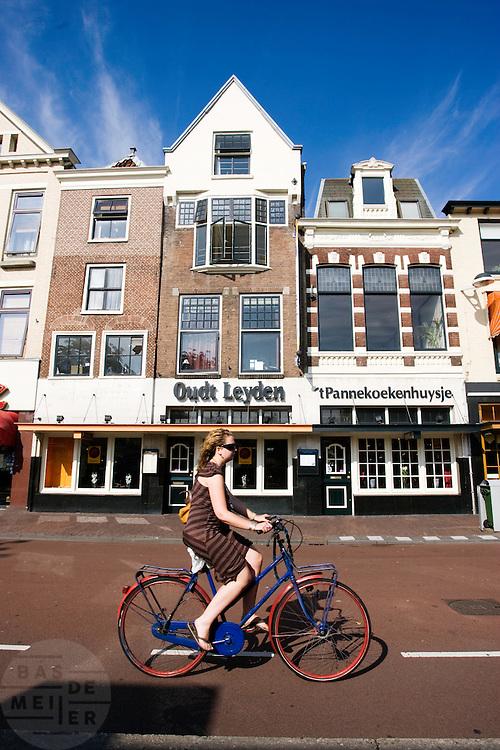 Een meisje fietst voorbij een pannenkoekenrestaurant in Leiden.<br /> <br /> A young woman is cycling at the center of Leiden.