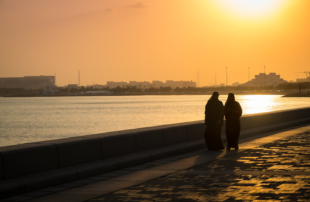 DOHA, QATAR - CIRCA DECEMBER 2013: People walking in the famous Corniche in Doha at sunset.