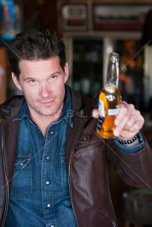 all american man sitting in a bar holding a beer