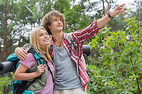 Young male hiker showing something to woman in forest