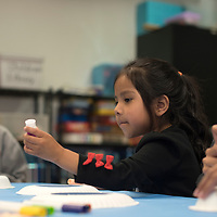 040415      Cayla Nimmo<br /> <br /> Tyana Yazzie creates an &quot;Easter bonnet&quot; out of a paper bowl and plate at the Spring Fling celebration held at the Octavia Fellin Library Children's branch in Gallup Saturday.
