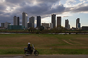A man rides a moded along Tamagawa Riverbanks witht he skyscrapers of Musashi Kosugi behind. Tamagawa, Tokyo, Japan, Friday December 14th 2018
