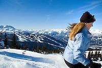 A woman, 40-50, skis Blackcomb Mountain winter day, Whistler mountain behind, Whistler, BC Canada.