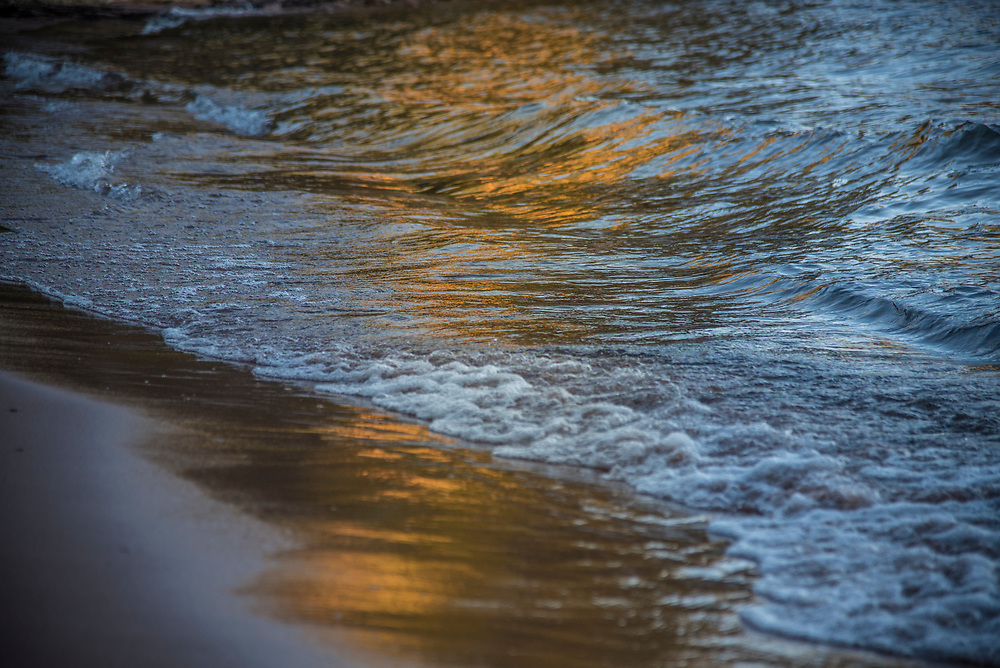 Fall color reflects on the wet sand of Wetmore Beach near Marquette, Michigan as Lake Superior waves crash.