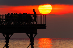© Licensed to London News Pictures.29/03/2019. Aberystwyth, UK. A group of people enjoying an evening drink at the end of the pier in Aberystwyth, on the Cardigan Bay coast of west Wales are silhouetted by the flaming setting sun . High pressure continues to dominate the weather for much England and Wales, with settled conditions forecast to last at least another day , before more cooler conditions return. Photo:Keith Morris/LNP