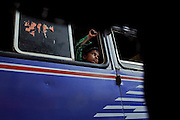 A young boy is sitting on a bus driving on the streets of Bhopal, Madhya Pradesh, India, near the abandoned Union Carbide (now DOW Chemical) industrial complex.