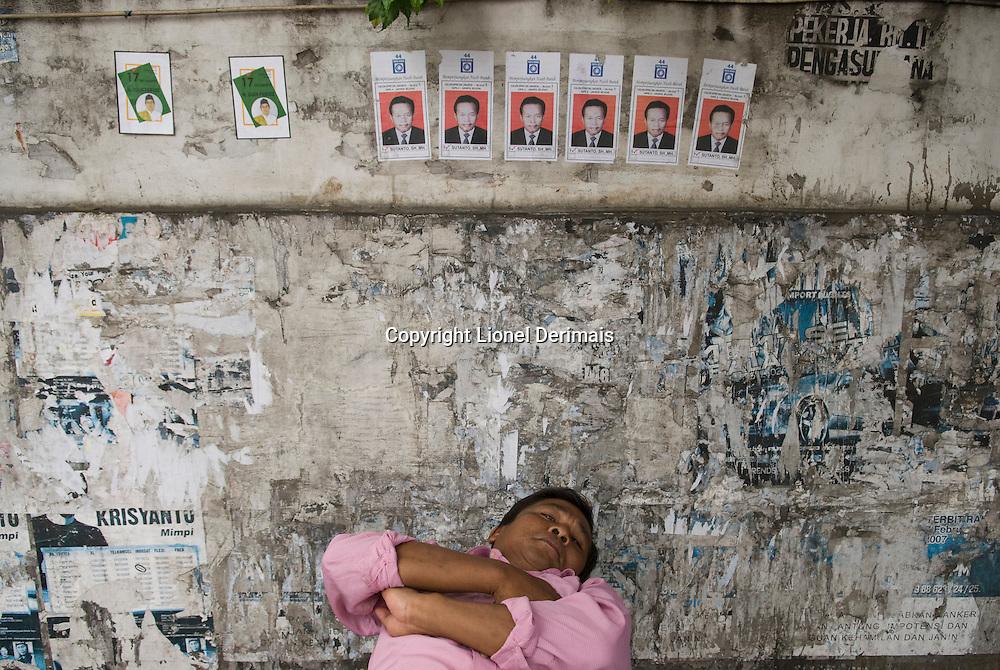 Man sleeping with election posters. Homme dormant avec des posters pour un candidat a l'election legislative du 9 avril 2009.