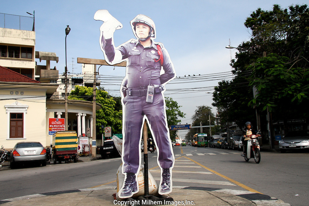 Fake traffic police stands in the middle of Bangkok intersection to slow down motorists.