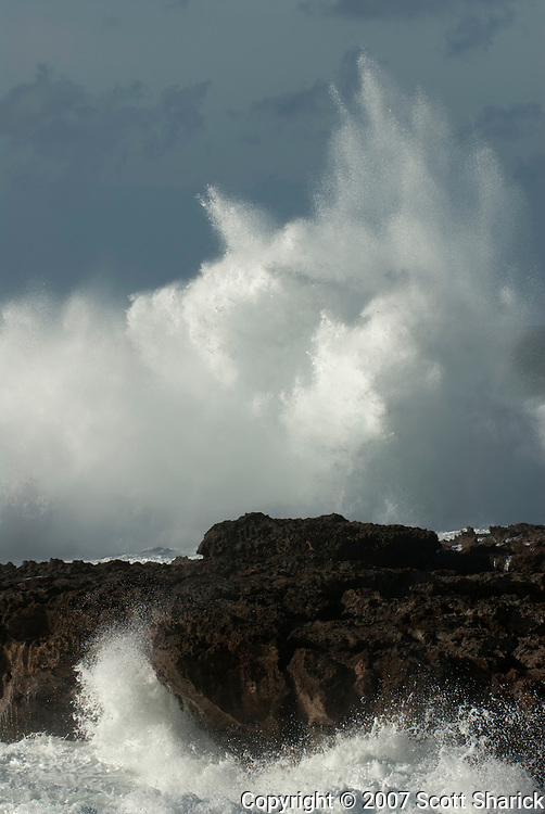 An ocean wave crashes on the rocky shore of the North Shore of Oahu, Hawaii