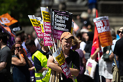 "© Licensed to London News Pictures . 07/07/2018 . Leeds , UK . Anti Fascist counter-protesters hand out placards during an anti-Islam demonstration by supporters of jailed EDL founder Tommy Robinson , including those from the "" Yorkshire Patriots "" and "" First for Britain "" , in Leeds City Centre . Robinson ( real name Stephen Yaxley-Lennon ) was convicted of Contempt of Court in May 2018 after committing a second offence , whilst serving a suspended sentence for the same crime . Photo credit : Joel Goodman/LNP"