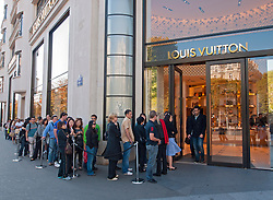 Queue of shoppers outside Louis Vuitton store on Champs Elysees in Paris France