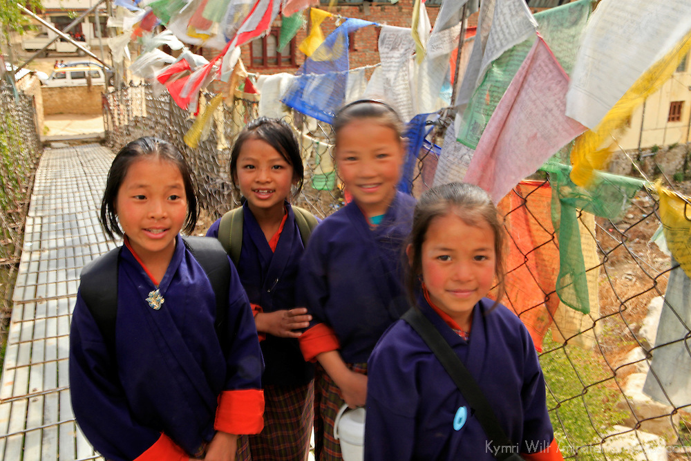 Asia, Bhutan, Paro. Young Bhutanese school girls cross bridge of prayer flags.