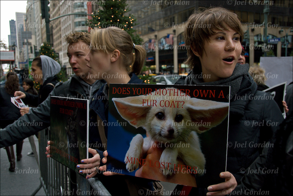 Young Animal Rights activits, protesters with sign &quot;Do Your Mother Own A Fur Coat? Mine Lost Hers&quot;. <br /> <br /> Every year on the day after Thanksgiving for the last two decades, thousands of people around the U.S. have held demonstrations, marches, vigils and other activities for Fur Free Friday to protest a global multi-billion dollar industry that kills over 40 million animals annually.<br /> <br /> The suffering and deaths of feeling animals is not worth the price of an expensive coat or the fur trim on a jacket collar, so don't pay for the blood of innocent animals.