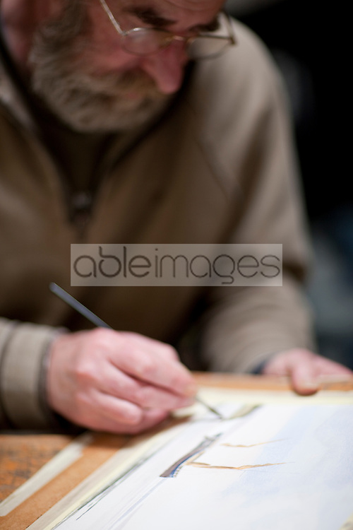 Close up of an artist painting at his desk