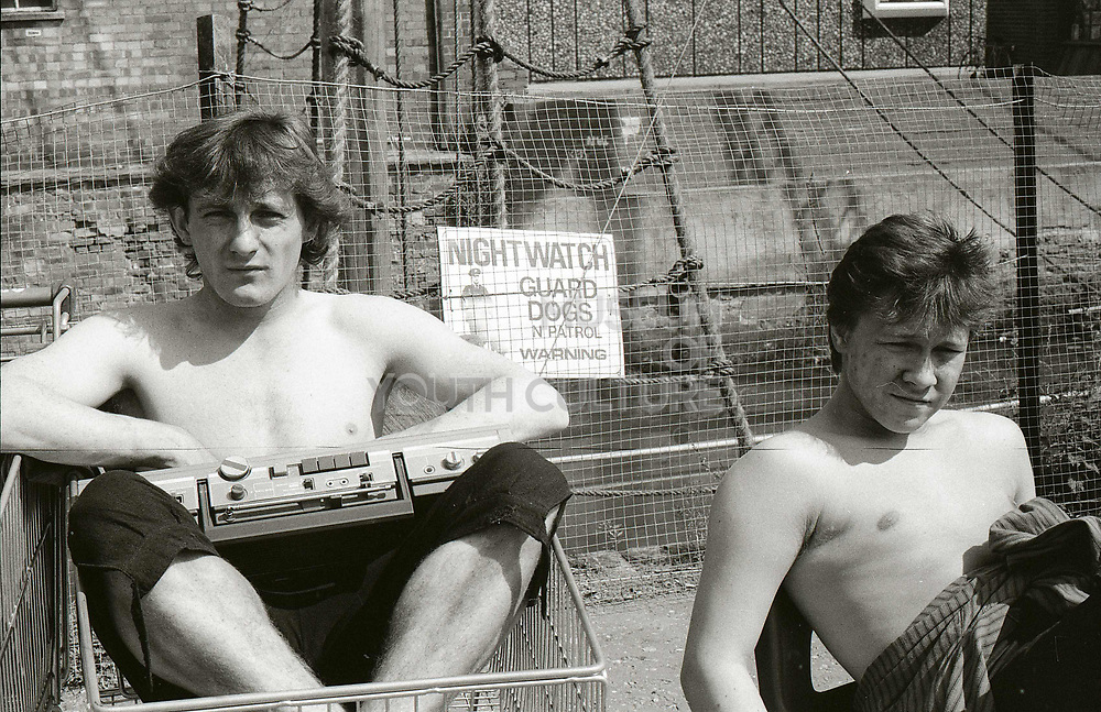 Shirtless men with cassette player, London. 1980s.