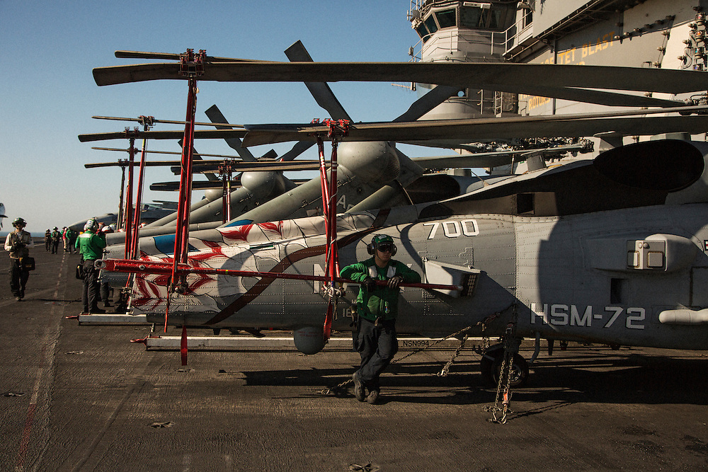A flight deck crew member rests in the shade of a helicopter following flight operations<br /> <br /> Aboard the USS Harry S. Truman operating in the Persian Gulf. February 25, 2016.<br /> <br /> Matt Lutton / Boreal Collective for Mashable