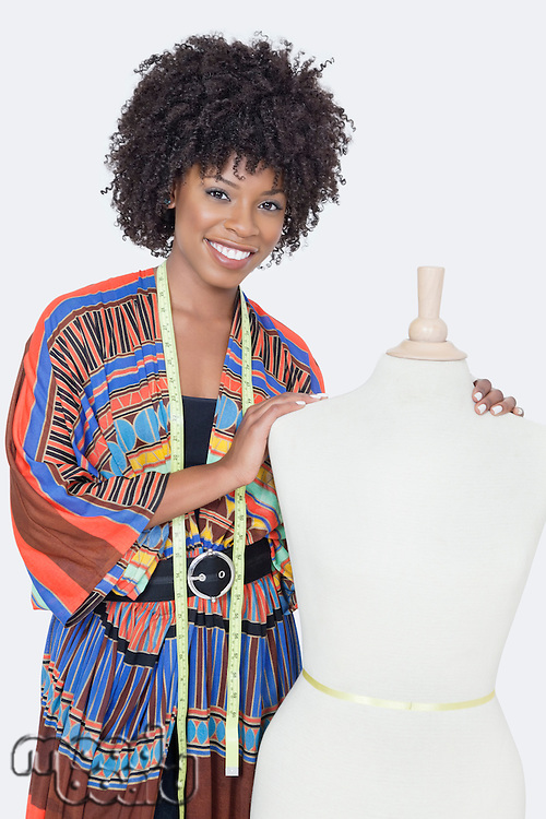 Portrait of African American female fashion designer with tailor's dummy over gray background