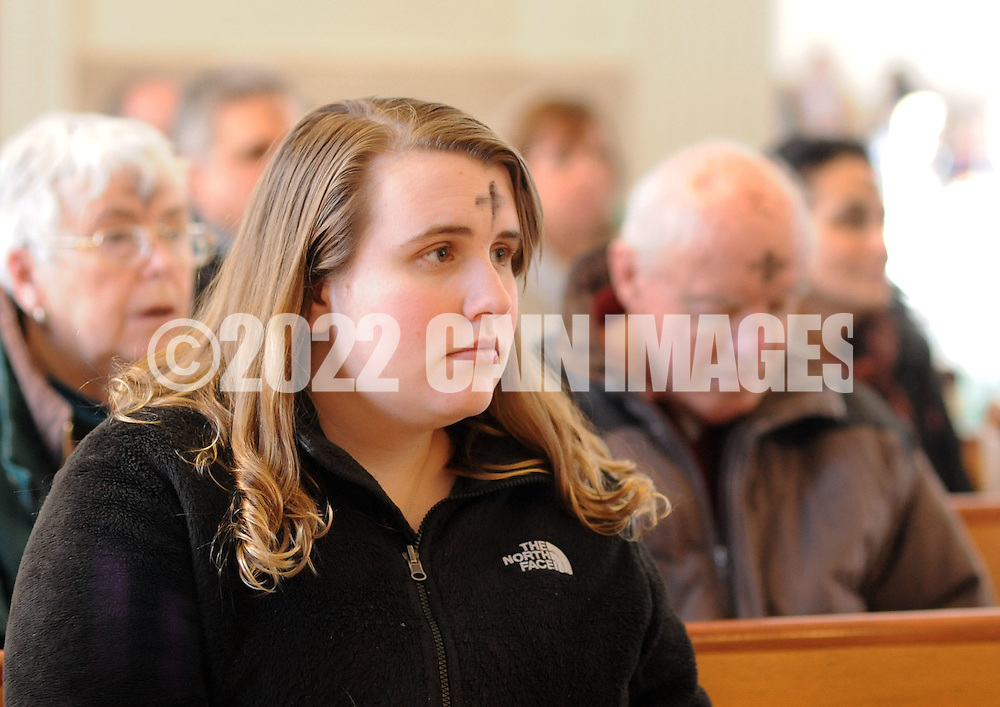 DOYLESTOWN, PA - FEBRUARY 18: Katie Conway, 22 of Doylestown, Pennsylvania sits in a pew after receiving ashes on her forehead for Ash Wednesday at Our Lady of Mt. Carmel Catholic Church February 18, 2015 in Doylestown, Pennsylvania. (Photo by William Thomas Cain/Cain Images)